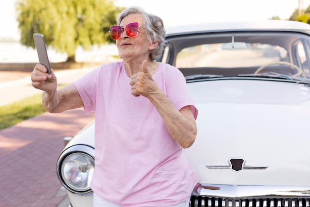 Glückliche ältere frau, die neben ihrem auto steht