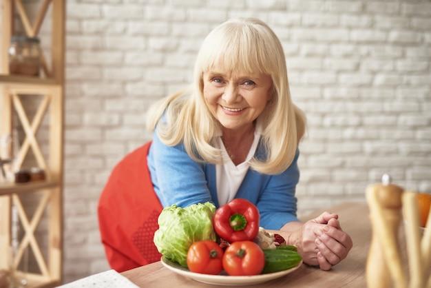 Glückliche ältere frau, die selbst angebautes gemüse genießt.