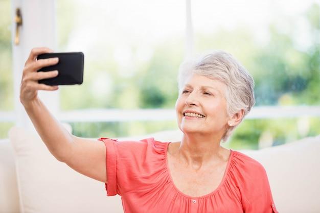 Glückliche ältere frau, die selfie auf dem sofa nimmt