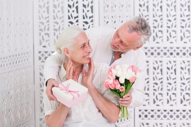 Glückliche ältere frau, die überraschtes geschenk von ihrem liebevollen ehemann empfängt