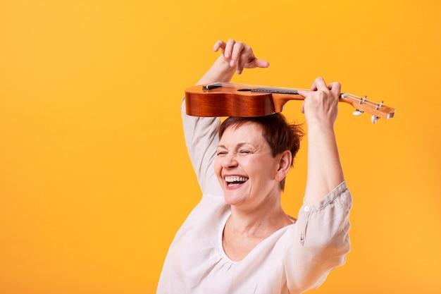 Glückliche ältere frau, die ukulele spielt