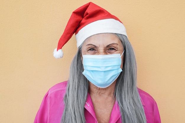 Glückliche ältere frau, die weihnachtsmütze mit schützender gesichtsmaske trägt - fokus auf gesicht