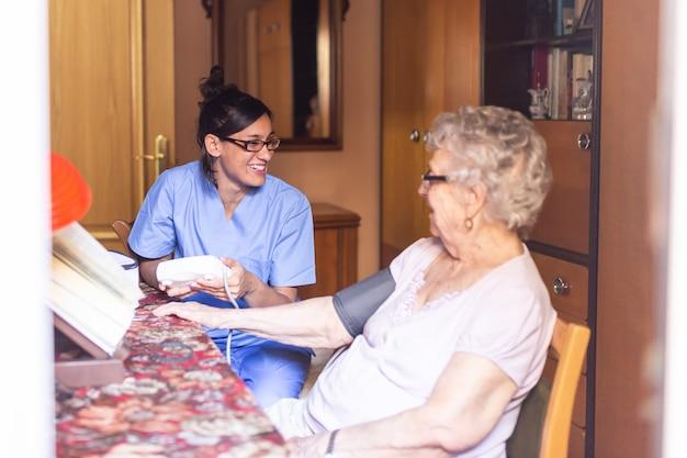 Glückliche ältere frau, die zu hause den blutdruck von ihrer pflegekraft nimmt