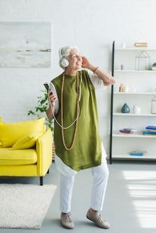 Glückliche ältere frau, die zu hause musik auf kopfhörer genießt