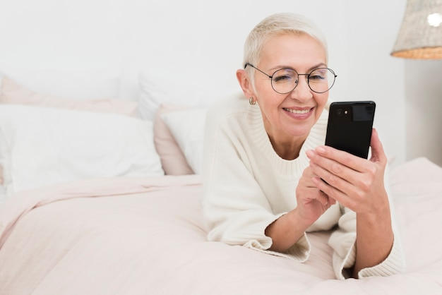 Glückliche ältere frau im bett, das smartphones hält