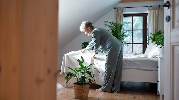 Glückliche ältere frau im bett zu hause, die morgens aufsteht und ein bett macht.