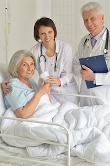 Glückliche ältere frau im krankenhaus mit fürsorglichen ärzten