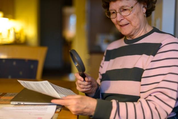 Glückliche ältere frau lächelnd beim lesen von papier mit lupe im esszimmer