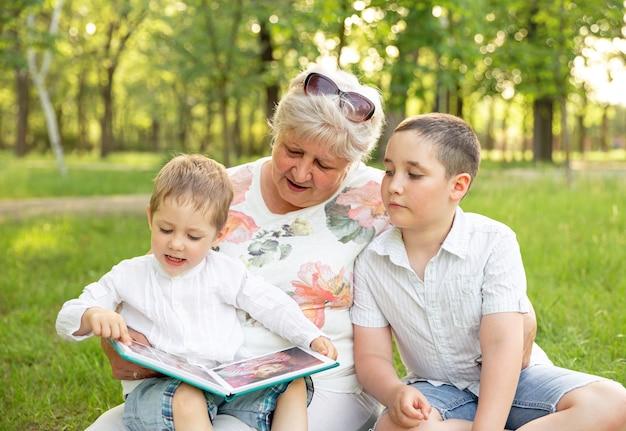 Glückliche ältere frau lächelnd, die ihre niedlichen enkelkinder wegschaut