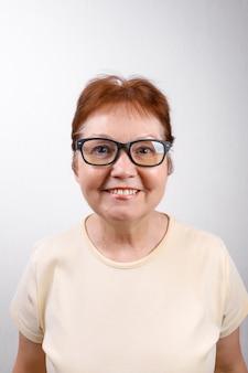 Glückliche ältere frau mit brille auf weiß in einem hellen t-shirt.