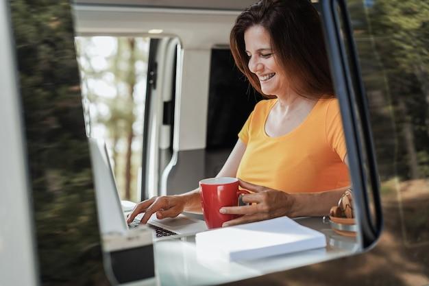 Glückliche ältere frau mit computer-laptop im wohnmobil-minivan - fokus auf gesicht