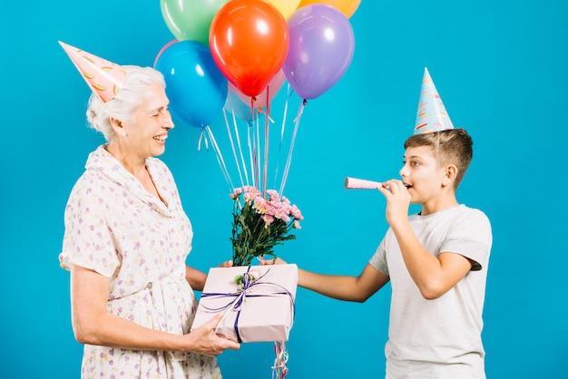 Glückliche ältere frau mit dem geburtstagsgeschenk und -blumen, die ihr schlagparteihorn des enkels betrachten