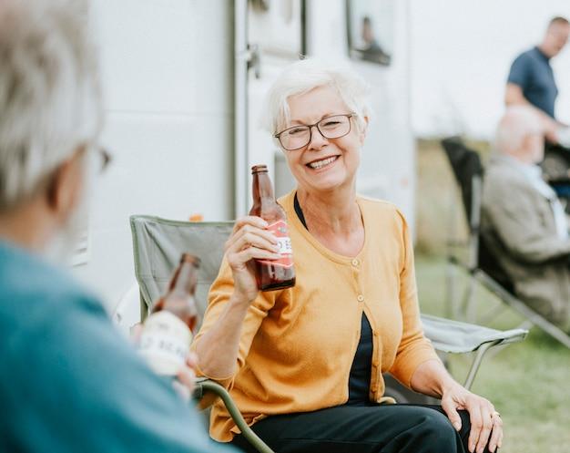 Glückliche ältere frau mit einer flasche bier