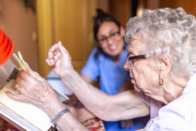 Glückliche ältere frau mit ihrer pflegekraft zu hause, die ein buch liest