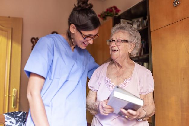 Glückliche ältere frau mit ihrer pflegekraft zu hause, die ein buch und ein lächeln hält