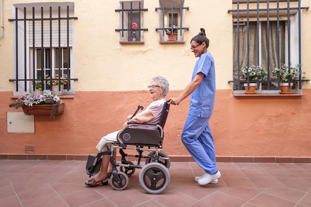 Glückliche ältere frau mit spazierstock im rollstuhl mit ihrer pflegekraft zu hause