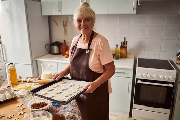 Glückliche ältere frau posiert mit einem tablett mit keksen