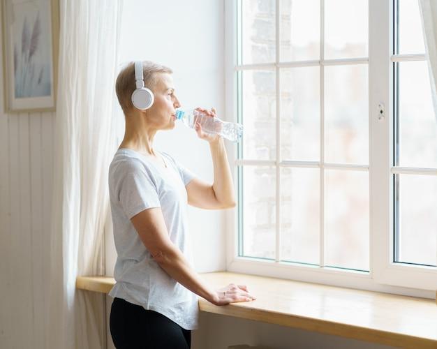 Glückliche ältere frau trinkt wasser aus plastikflasche nach dem sporttraining
