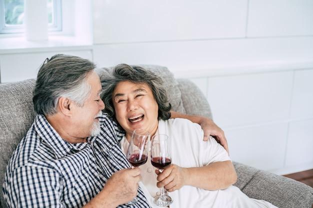 Glückliche ältere frau und ihr trinkender wein und glück des ehemanns