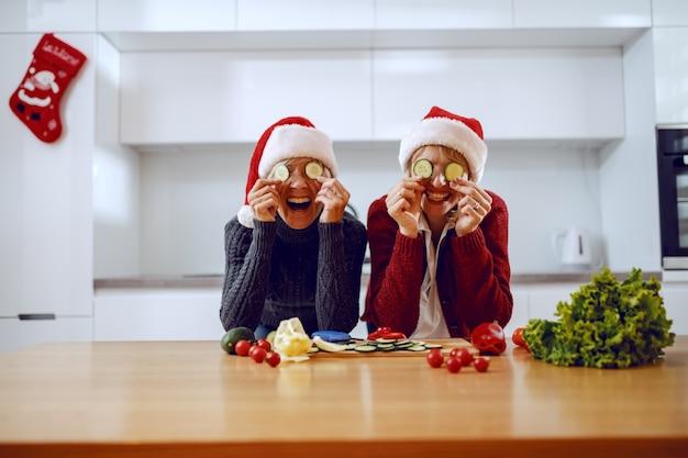 Glückliche ältere frau und ihre tochter, die auf küchentheke lehnen und gurkenscheiben auf augen halten. beide haben weihnachtsmützen auf den köpfen. auf der küchentheke steht gemüse.