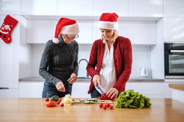 Glückliche ältere frau und ihre tochter, die mahlzeit für silvester vorbereiten. beide haben weihnachtsmützen auf den köpfen. tochter hackt roten pfeffer. auf der küchentheke steht gemüse. innenausstattung der wohnküche.