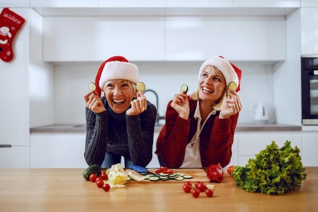 Glückliche ältere frau und ihre tochter, die sich auf küchentheke stützen und gurkenscheiben halten. beide haben weihnachtsmützen auf den köpfen. auf der küchentheke steht gemüse.