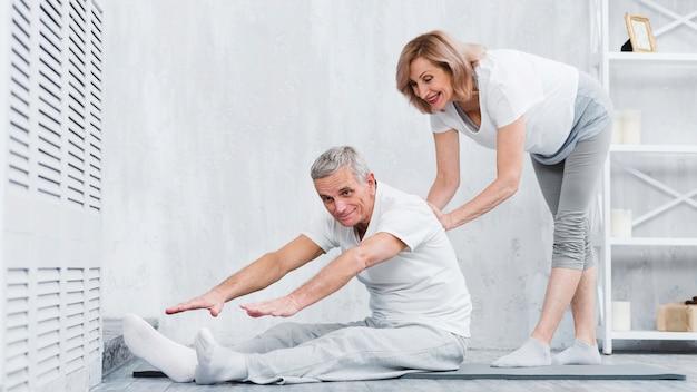 Glückliche ältere frau zu hause, die pensionären hilft, verbinden, um korrekte position einzunehmen