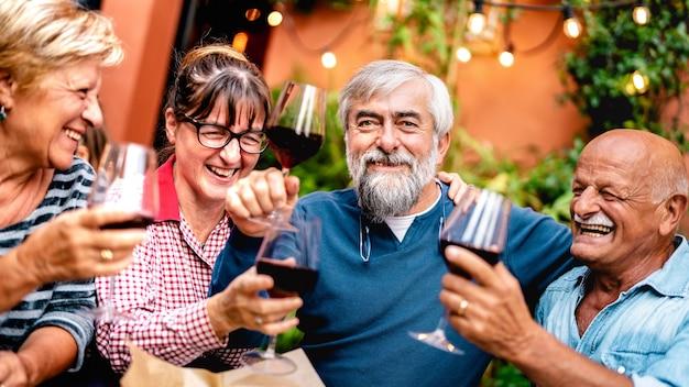 Glückliche ältere freunde, die spaß haben, rotwein auf der dinnerparty zu rösten - konzentrieren sie sich auf bärtigen mann
