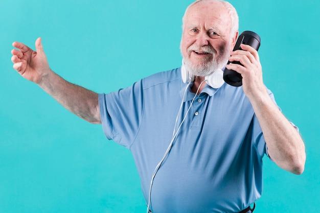 Glückliche ältere hörende musik am sprecher