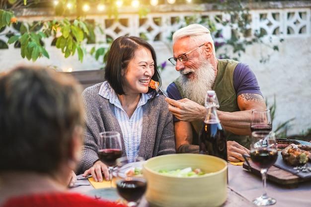 Glückliche ältere leute, die spaß am grillabendessen haben