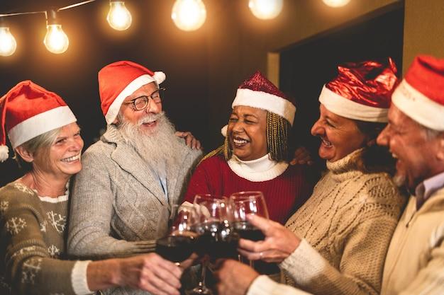Glückliche ältere leute, die weihnachtszeit feiern, trinken wein zusammen