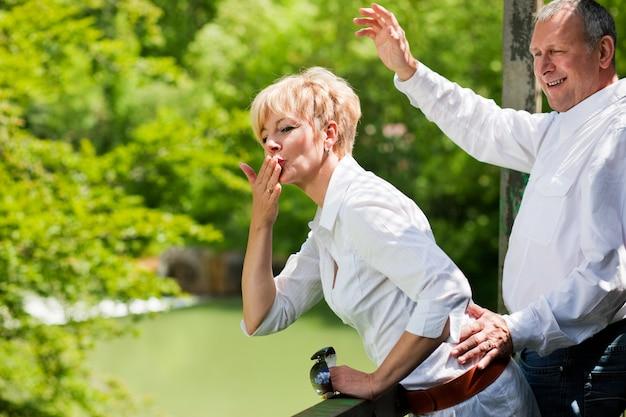 Glückliche ältere paare auf wellenartig bewegenden händen der brücke