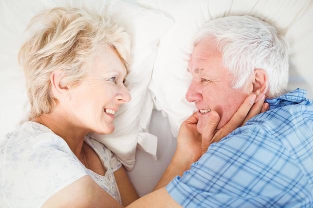Glückliche ältere paare, die auf bett liegen