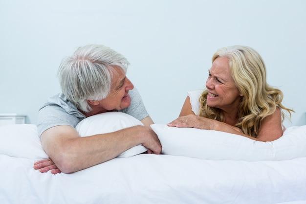 Glückliche ältere paare, die auf bett sich entspannen