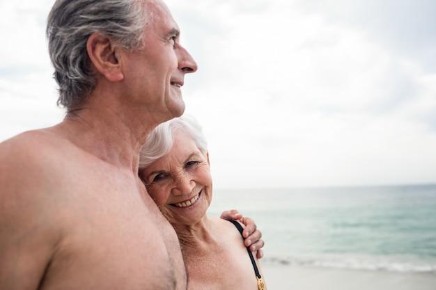 Glückliche ältere paare, die auf dem strand umfassen