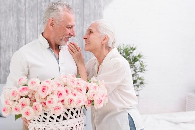 Glückliche ältere paare, die einander betrachten, korb von rosen in der hand halten