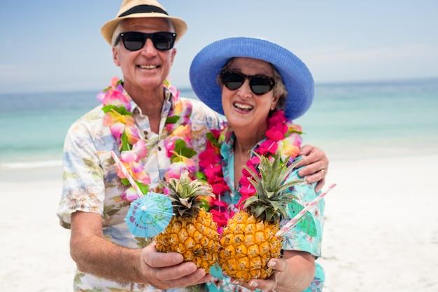 Glückliche ältere paare, die eine girlande tragen und ananascocktail halten