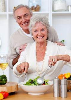 Glückliche ältere paare, die einen salat in der küche eeating sind