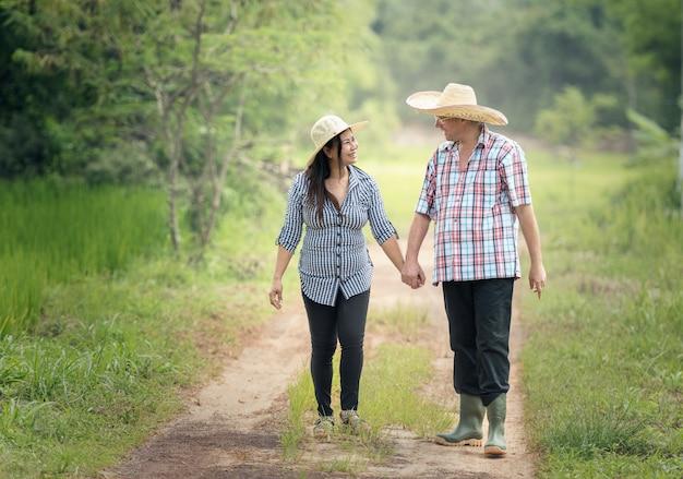 Glückliche ältere paare, die einen spaziergang in der sommerlandschaft machen
