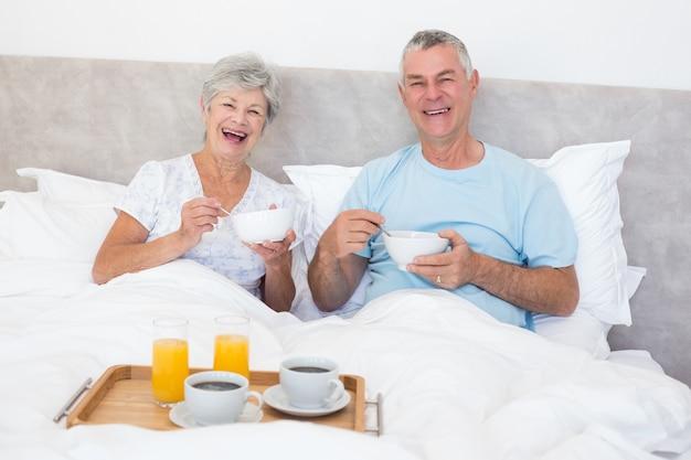 Glückliche ältere paare, die im bett frühstücken