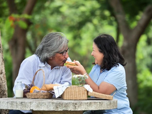 Glückliche ältere paare, die im gartenhaus picknicken.