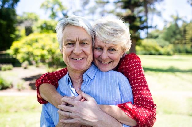 Glückliche ältere paare, die im park umfassen