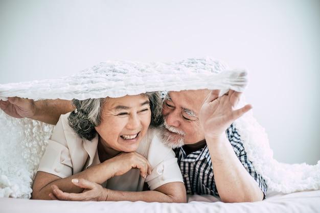 Glückliche ältere paare, die im schlafzimmer lachen
