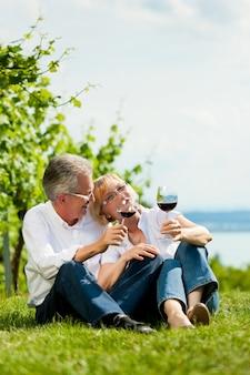 Glückliche ältere paare, die im trinkenden wein des grases sitzen
