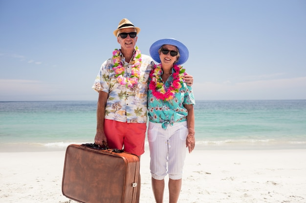 Glückliche ältere paare, die koffer auf dem strand halten