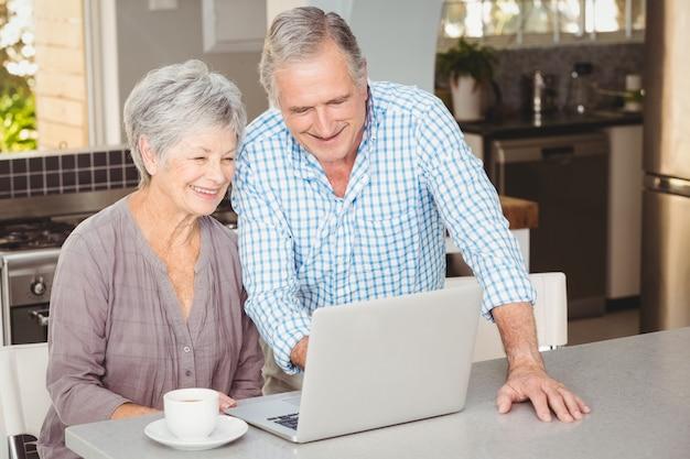 Glückliche ältere paare, die laptop betrachten