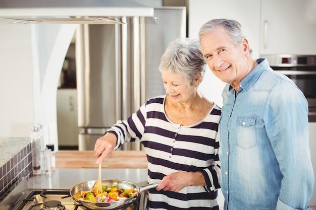 Glückliche ältere paare, die lebensmittel kochen