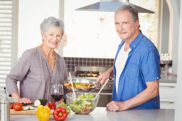 Glückliche ältere paare, die nahrung zubereiten