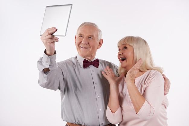 Glückliche ältere paare, die selbstporträt auf computertablette tun.