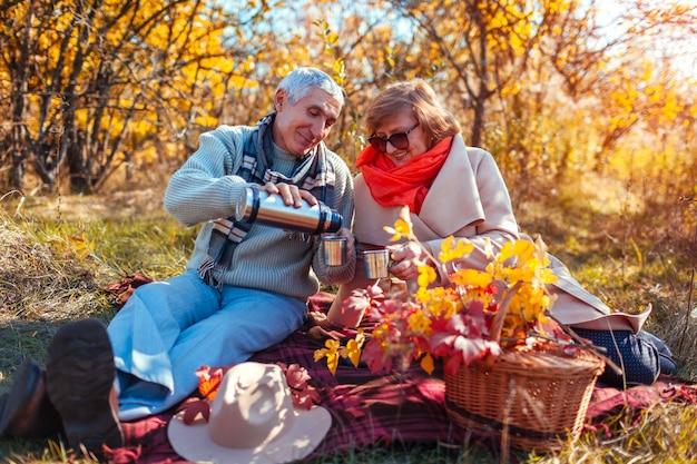 Glückliche ältere paare, die tee im herbstwald trinken und picknick genießen